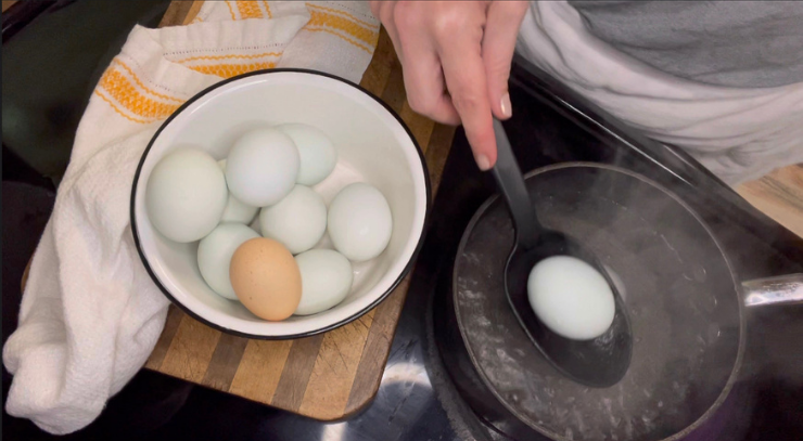 woman using a slotted spoon to put fresh eggs into a pot of boiling water to make hard boiled eggs for perfect easy-to-peel-hardboiled eggs everytime Keto On the RIse blog post.
