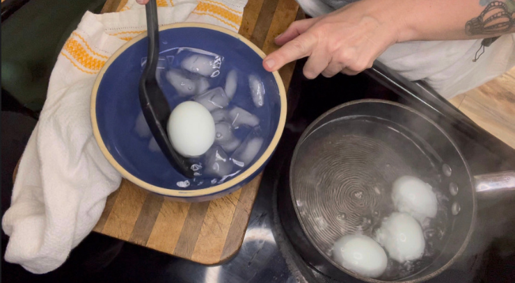 woman removing hardboiled eggs from a pot of boiling water to an ice bath for perfect easy-to-peel-hardboiled eggs everytime Keto On the RIse blog post.