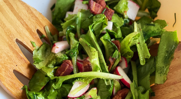 wilted lettuce with radishes and green onions in a bowl with salad tongs for the keto on the rise blog post wilted lettuce salad with hot bacon dressing