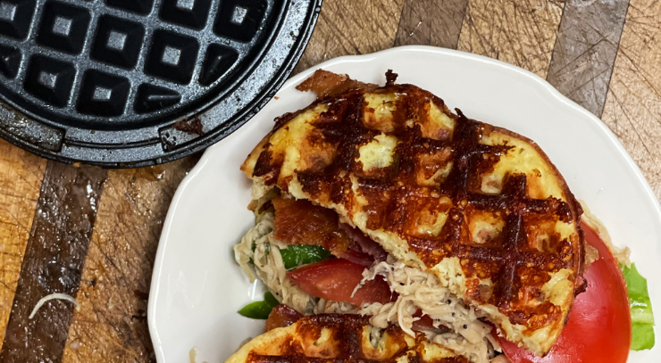 waffle maker on a cutting board and a chicken bacon ranch keto chaffle sandwich for the keto on the rise blog