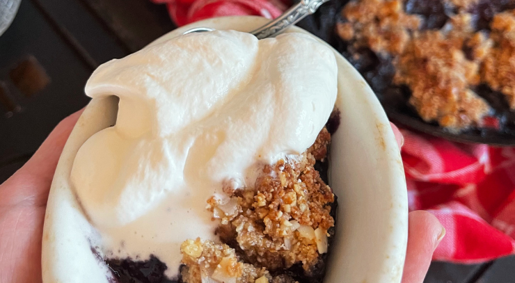 picture of a woman's hand holding   a white bowl that contains skillet berry crispy with keto vanilla whipped cream for the blog keto on the rise
