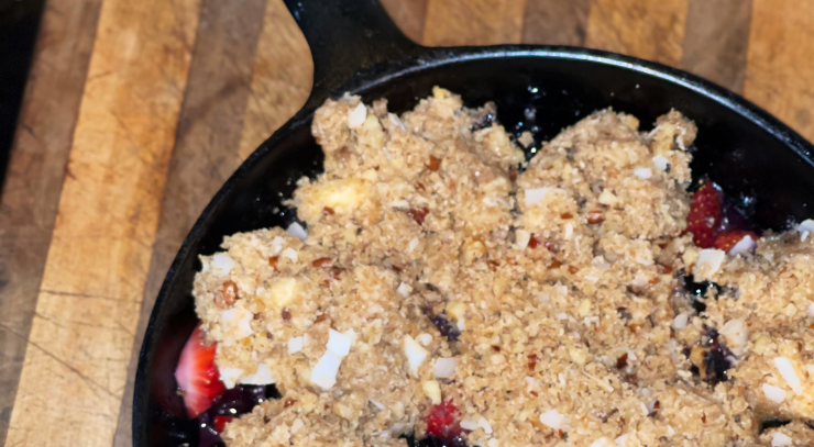 cast iron skillet sitting on a brown cutting board filled with skillet berry crisp for the blog keto on the rise