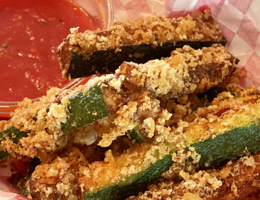 amazing crispy keto zucchini fries in a red basket with a small bowl of marinara sauce for the blog keto on the rise