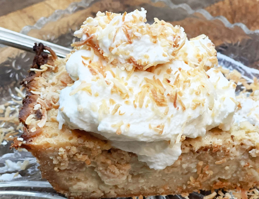 triple coconut cream pie on a glass plate with toasted coconut around the pie for the blog keto on the rise